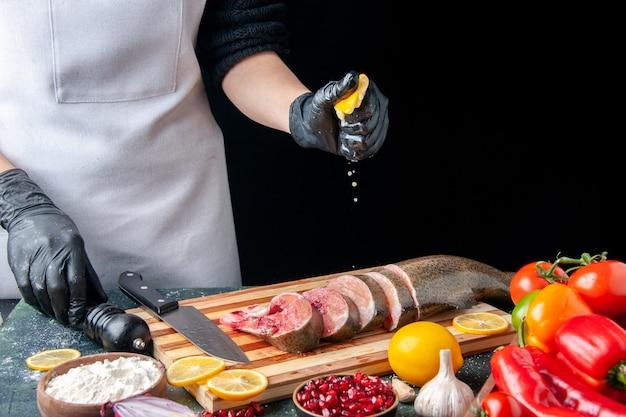 Vooraanzicht chef-kok knijpt citroen op rauwe vis plakjes mes op snijplank groenten op houten serveerplank op keukentafel