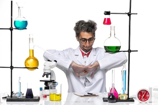 Vooraanzicht chemicus op middelbare leeftijd in wit medisch kostuum dat voor het werk voorbereidingen treft