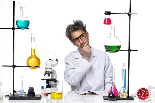 Vooraanzicht chemicus van middelbare leeftijd in witte medische pakzitting met oplossingen het denken