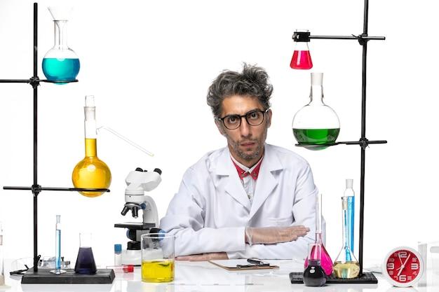 Vooraanzicht chemicus van middelbare leeftijd in witte medische pakzitting met oplossingen