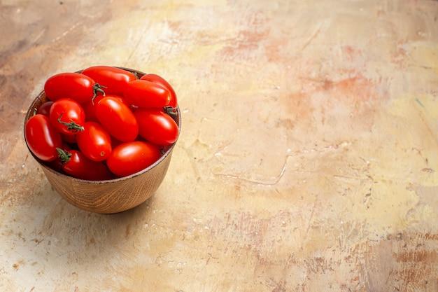 Vooraanzicht cherrytomaatjes in houten kom op amberkleurige vrije ruimte
