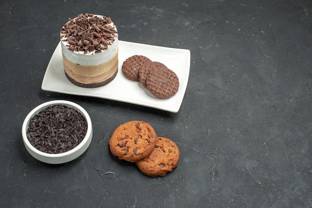 Vooraanzicht chocoladetaart en koekjes op witte rechthoekige plaatkom met donkere chocoladekoekjes op donker