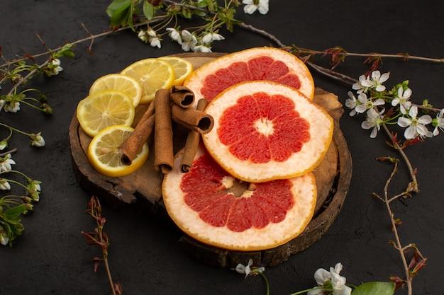 Vooraanzicht citrus gesneden citroen en grapefruit vers mellow rijp op de bruine houten bureau en grijze vloer