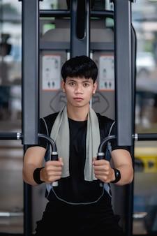 Vooraanzicht, close-up portret jonge knappe man in sportkleding die zit voor het doen van machine-borstpersoefening in moderne sportschool, vooruitkijkend,