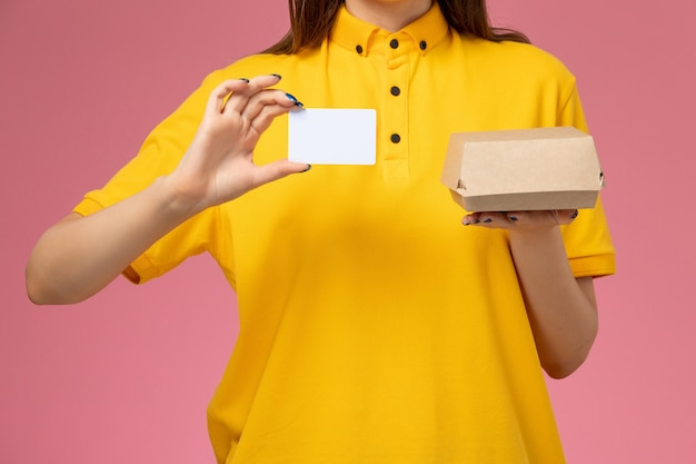Vooraanzicht close-up vrouwelijke koerier in geel uniform en cape die weinig voedselpakket en kaart vasthoudt op lichtroze muur, baan service uniform bezorgbedrijf