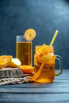 Vooraanzicht cocktail gesneden sinaasappelen en appels op een houten bord op dark Gratis Foto