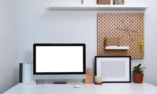 Vooraanzicht computer met leeg scherm, kamerplant leeg fotolijstje en kantoorbenodigdheden op witte tafel.