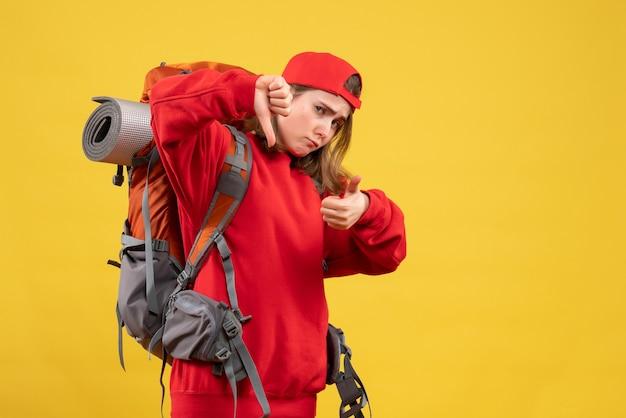 Vooraanzicht coole vrouwelijke reiziger met rugzak gebaren duimen op en neer borden