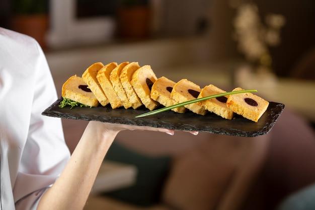 Vooraanzicht dat van chef-kok een heerlijke voedselplaat houdt