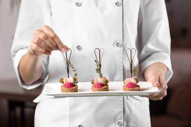 Vooraanzicht dat van chef-kok een voedselplaat houdt