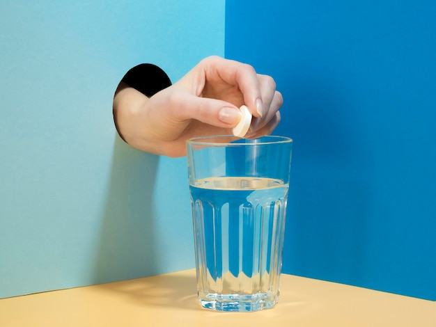 Vooraanzicht dat van hand bruisende tablet laat vallen in glas water