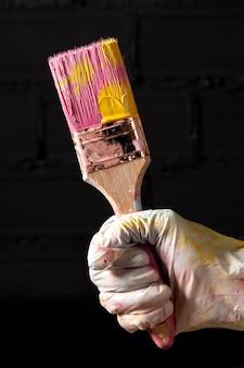 Vooraanzicht dat van hand gekleurde verfborstel houdt