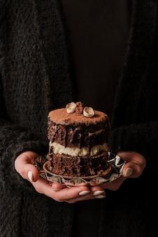 Vooraanzicht dat van handen cake houdt