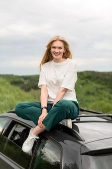 Vooraanzicht dat van smileyvrouw zich op auto bevindt