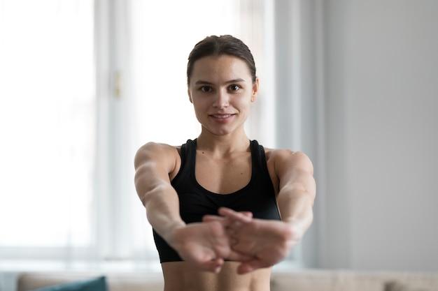 Vooraanzicht dat van sportieve vrouw haar wapens uitrekt