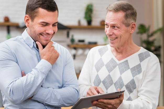 Vooraanzicht dat van vader zijn zoon de tablet toont