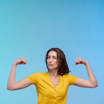Vooraanzicht dat van vrouw haar bicepsen met exemplaarruimte toont