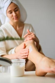 Vooraanzicht dat van vrouw lotion thuis op benen toepast
