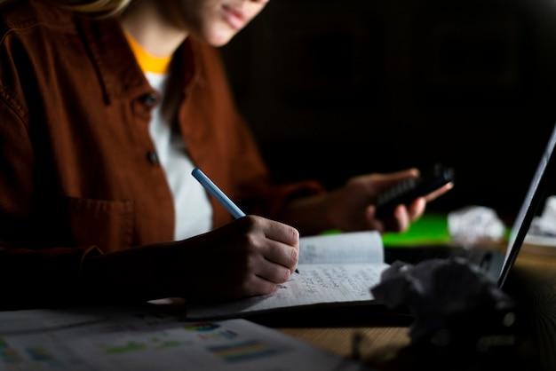 Vooraanzicht dat van vrouw op notitieboekje opmerkt