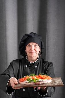 Vooraanzicht dat van vrouwelijke chef-kok schotel voorstelt