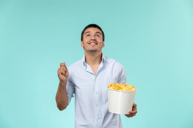 Vooraanzicht de jonge mannelijke mand met chips op blauw bureau