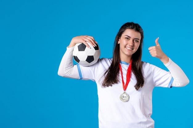 Vooraanzicht de jonge vrouwelijke voetbalbal op blauwe muur