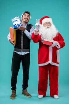 Vooraanzicht de kerstman met jong mannetje en stelt op blauw bureau voor