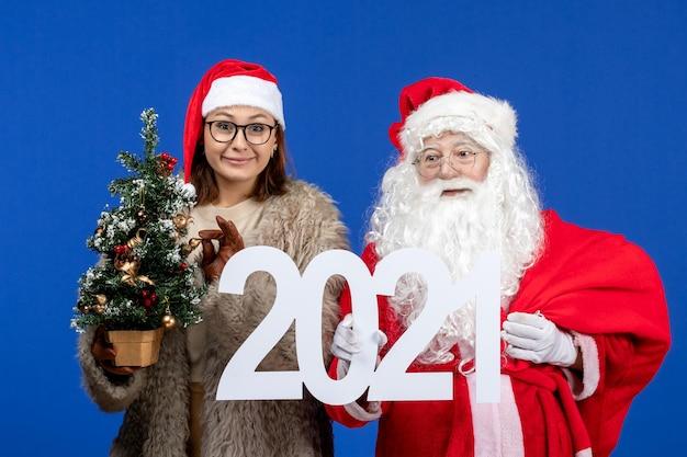 Vooraanzicht de kerstman met vrouwelijk schrijven en kleine kerstboom op blauwe kleur nieuwjaar