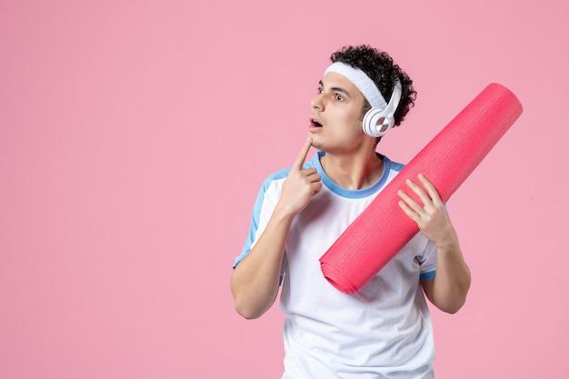 Vooraanzicht denken jong mannetje in sportkleren met yogamat en hoofdtelefoons