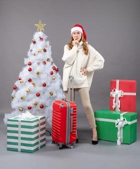 Vooraanzicht denken xmas vrouw met kerstmuts staande in de buurt van witte kerstboom