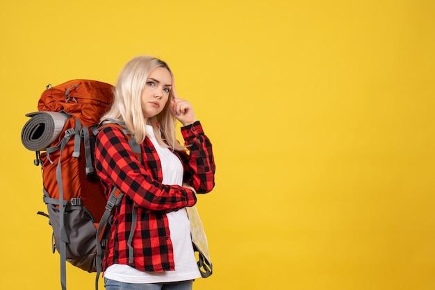 Vooraanzicht denkende blonde vrouw met haar rugzak die zich op gele muur bevindt