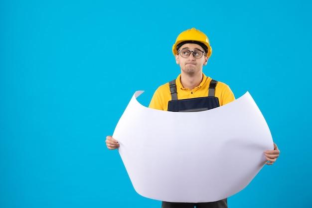 Vooraanzicht denkende mannelijke bouwer in geel uniform met plan op blauwe muur