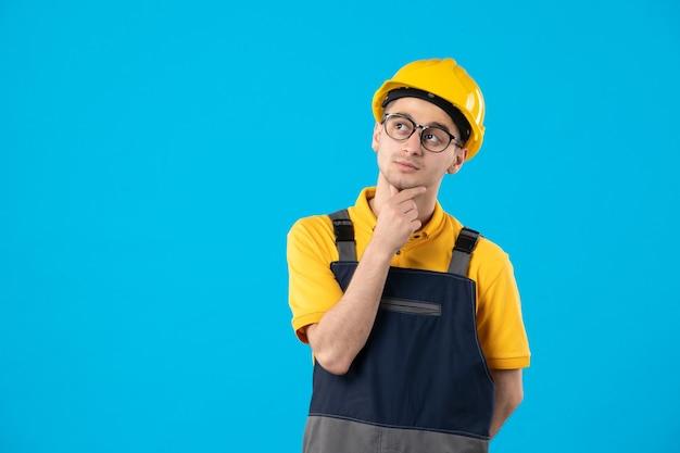 Vooraanzicht denkende mannelijke bouwer in geel uniform op blauwe muur
