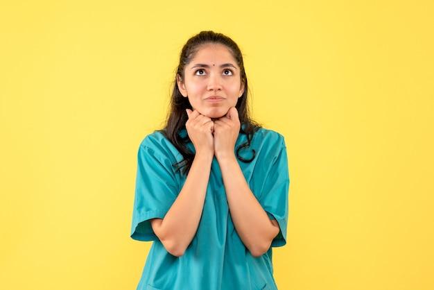 Vooraanzicht denkende vrouwelijke arts in uniform staande op gele geïsoleerde achtergrond