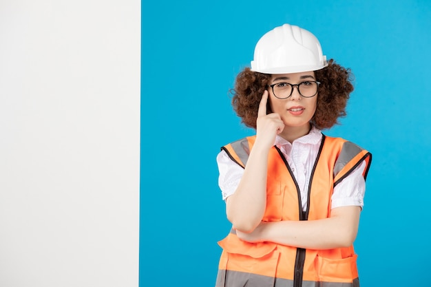 Vooraanzicht denkende vrouwelijke bouwer in uniform op blauwe muur