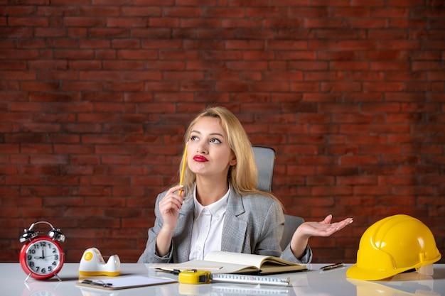Vooraanzicht denkende vrouwelijke ingenieur zittend op kantoor