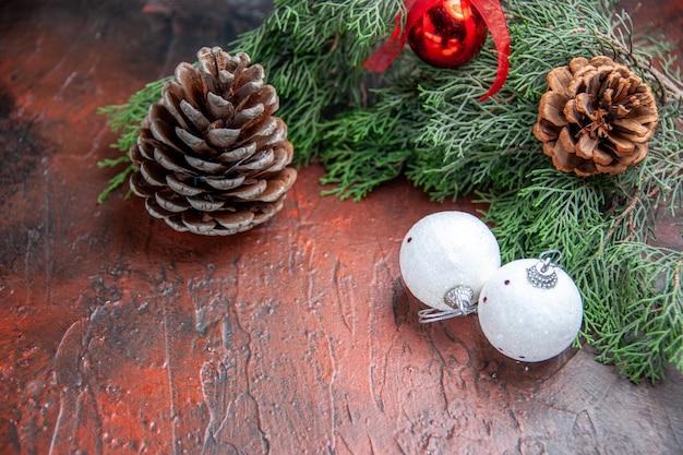 Vooraanzicht dennenappels dennenboom takken xmas bal speelgoed op donkerrode achtergrond vrije ruimte xmas foto