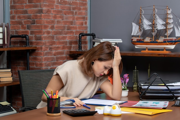 Vooraanzicht depressieve vrouw die op kantoor werkt