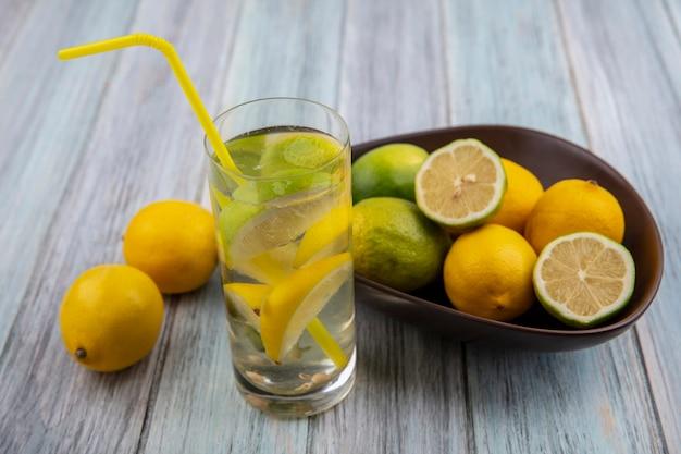 Vooraanzicht detoxwater in een glas met een geel rietje en limoenen (lemmetjes) met citroenen in een kom op een grijze achtergrond
