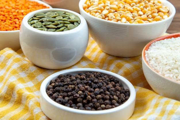 Vooraanzicht dichtbij verschillende rauwe grutten rijstkorrels linzen en boekweit in platen op bruin oppervlak