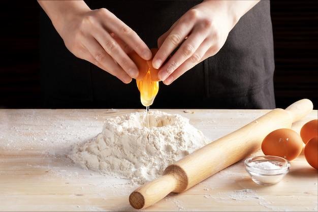 Vooraanzicht die van de handen van de vrouw recept met houten deegrol maken