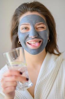 Vooraanzicht die van vrouw thuis het dragen van gezichtsmasker ontspannen