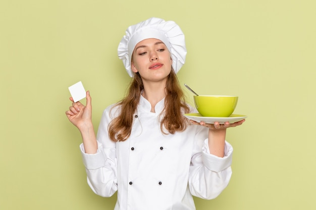 Vooraanzicht die van vrouwelijke kok in wit kokkostuum groene plaat op groene muur houden