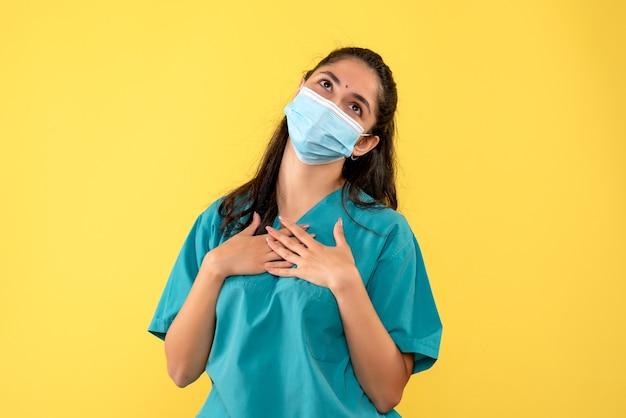 Vooraanzicht die vrouwelijke arts met masker wensen die handen op haar borst op gele achtergrond zetten