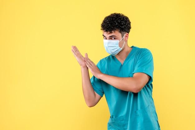 Vooraanzicht dokter de dokter in masker moedigt mensen aan om handen te wassen