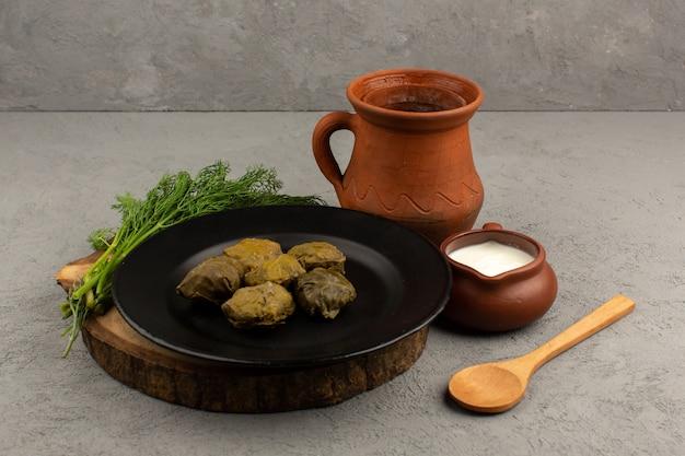 Vooraanzicht dolma beroemde oosterse maaltijd met gehakt in zwarte plaat op het bruine bureau en grijze vloer