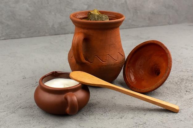 Vooraanzicht dolma samen met yoghurt in bruine potten op de grijze vloer