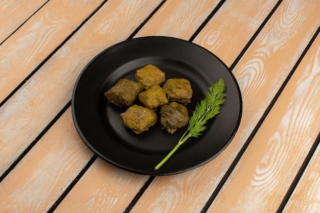 Vooraanzicht dolma smakelijke vleesmaaltijd in zwarte plaat op de rustieke houten vloer