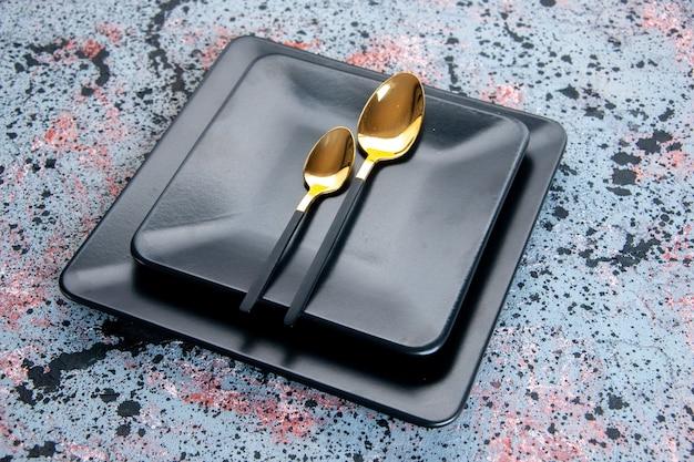 Vooraanzicht donkere borden met gouden lepels op lichte achtergrond