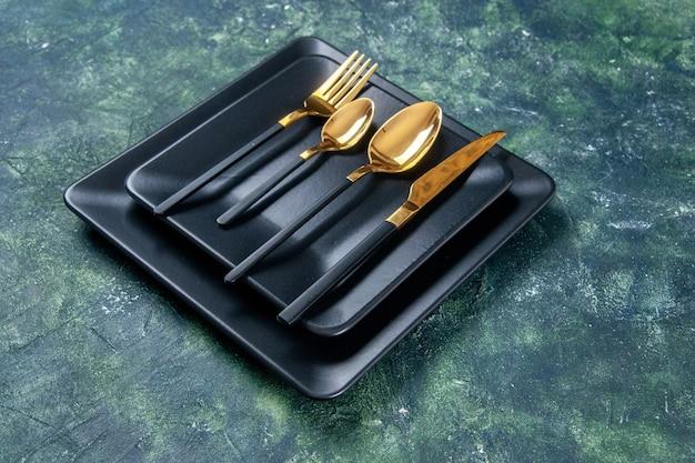 Vooraanzicht donkere platen met gouden lepels, vork en mes op donkere achtergrond